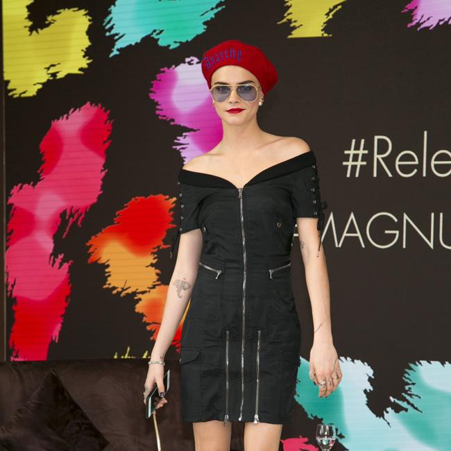 Cara Delevigne covers shaved head with red hat